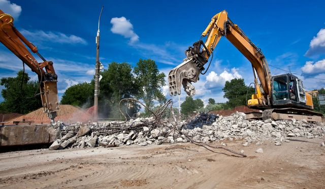 excavators demolishing concrete